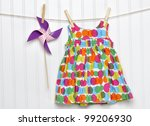 Baby Dress and Pinwheel on a Clothesline for Summer. - stock photo