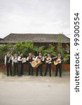 Small photo of Mariachi band in front of building playing their instruments