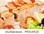 Closeup of grilled shrimps and tomatoes on bamboo sticks with salmon - stock photo