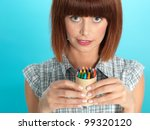 Small photo of beautiful young woman, holding abox of color crayons, smiling, on blue background