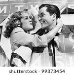 Closeup of couple bursting through calendar - stock photo