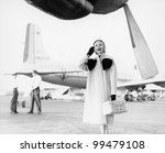 Young woman standing next to an airplane looking happy - stock photo