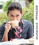 Asian woman drinking a coffee - stock photo