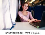 Young woman using her laptop computer while on the train (shallow DOF; color toned image) - stock photo
