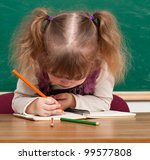 Cheerful smiling child with a book and apples against blackboard  in a class .  School concept - stock photo
