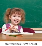 Cheerful smiling child with a book  against blackboard  in a class . Looking at camera. School concept - stock photo
