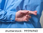 Businessman in black shirt crossing his fingers behind his back - stock photo