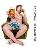 fat man eating hamburger seated on armchair - stock photo