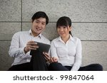 Two business people using a touch pad - stock photo