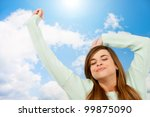 Young woman with eyes closed stretching arms on blue sky. - stock photo