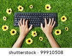 Closeup of hands typing on a computer keyboard. Shot outdoor on the lawn - stock photo