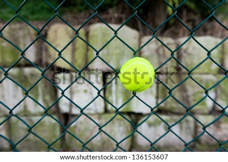 a ball stuck in a chain link wire fence at a tennis court
