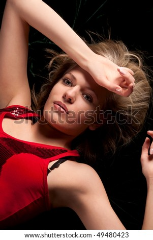 A beautiful blond woman lying in black background