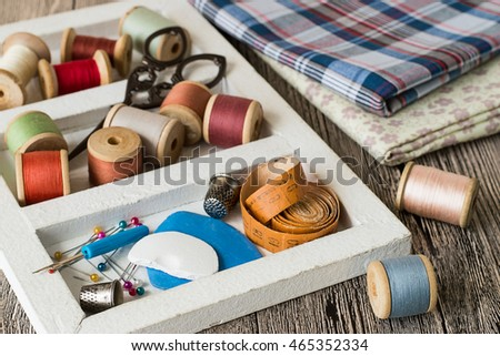 A box with sewing supplies,  pieces of fabric and sewing threads coils on a gray wooden table.