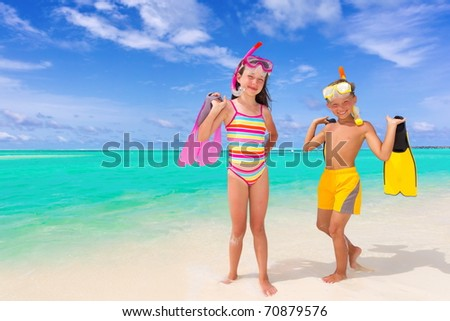 A boy and girl on a white, sandy beach with snorkeling gear.