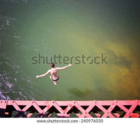 a boy jumping of an old train trestle bridge into a river   - stock photo