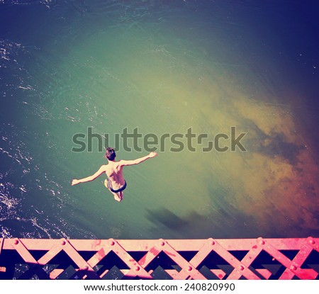 a boy jumping of an old train trestle bridge into a river toned with a retro vintage instagram filter effect   - stock photo