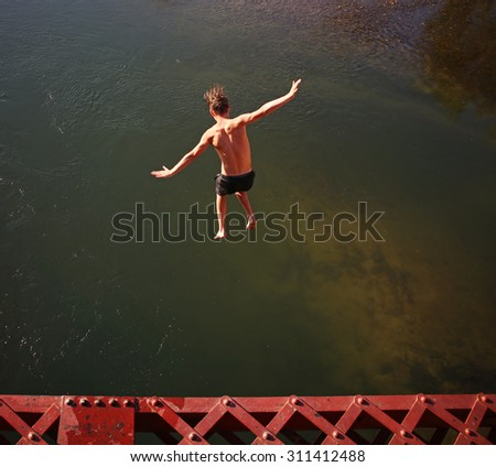 a boy jumping of an old train trestle bridge into a river toned with a retro vintage instagram filter effect app or action on a hot summer day - stock photo