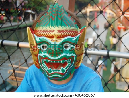 A boy wearing Thai Giant mask on the  bridge  overlooking the canal at a floating market in Thailand