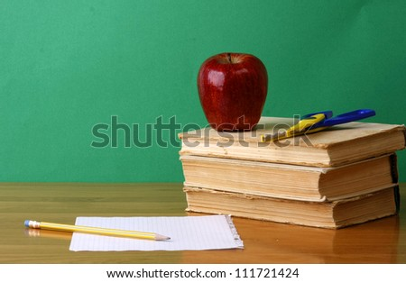 A chalkboard with an apple, a pencil and books - stock photo