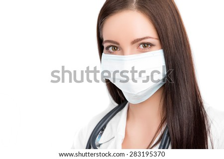 A close-up portrait of a pretty female doctor or nurse with stethoscope wearing a surgical mask  isolated on a white background - stock photo