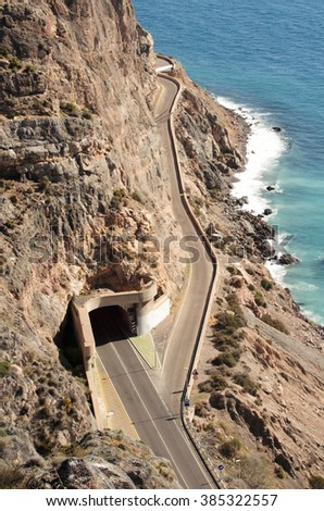 a coastal road bifurcates , one of the tracks passing through a tunnel and the other one continues along the coast