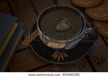 a cup of tea of glazed ceramics. On the saucer cinnamon stick and star anise. Three cookies and two books bound in blue. - stock photo