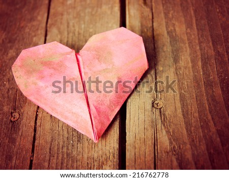 a discarded dirty paper origami heart on a wooden background toned with a vintage instagram filter effect applied (very shallow DOF on center crease) - stock photo