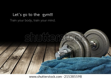 a dumbbell and a towel is on the wooden floor - stock photo