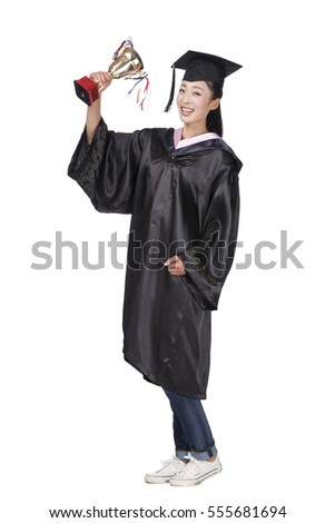 A female graduate in dressed holding a trophy