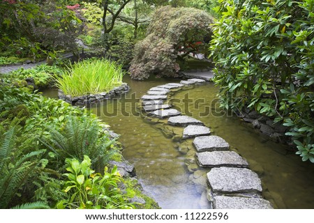 A footpath from stones laid with brick through a fine pond in Japanese garden - stock photo