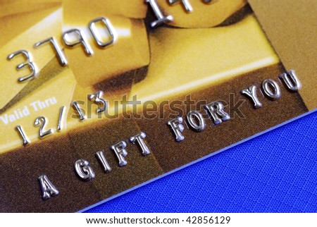 â??A Gift For Youâ? from a golden gift card isolated on blue - stock photo