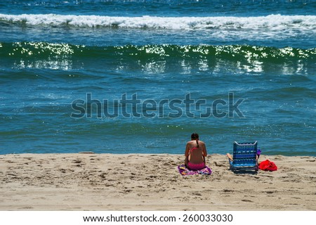 A girl enjoys quiet time on the beach on Long Beach Island in New Jersey. - stock photo