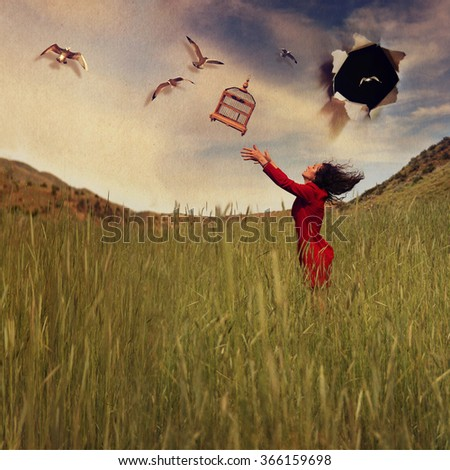 a girl in a field tossing a birdcage in the air toned with a retro vintage instagram effect app or action - stock photo