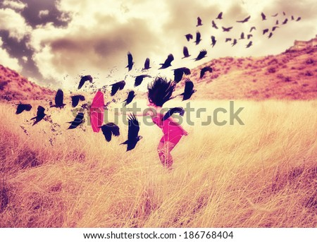 a girl in a field with an umbrella pointing toward a flock of birds done with a warm filter