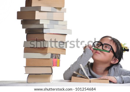 A girl looking at a pile of books with the hope to dive into the land of knowledge. - stock photo