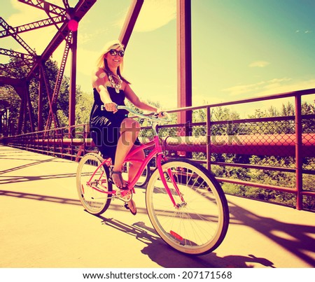 a  girl riding bikes on a bridge toned with a retro vintage instagram filter  - stock photo