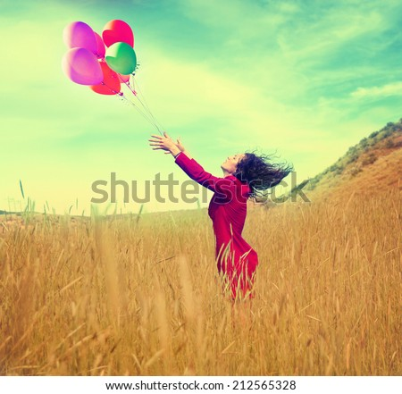 a girl walking in a field letting go of a bunch of balloons done with a vintage retro instagram filter effect - stock photo