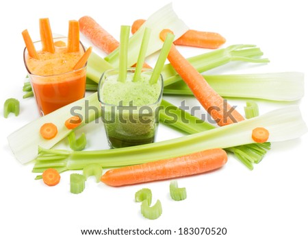 A glasses of fresh celery and carrot juices surrounded by vegetables isolated on white background.
