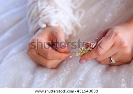 a hairpin in a bride hand ready to walk down the aisle on her wedding day . Selective focus on her left hand