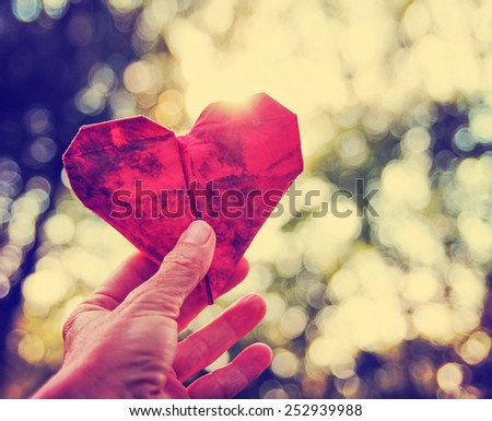 a hand holding an origami paper heart up to the sun during sunset toned with a vintage retro instagram filter effect  - stock photo