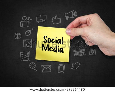 A hand holding Post-it note that says 'Social Media'. - stock photo