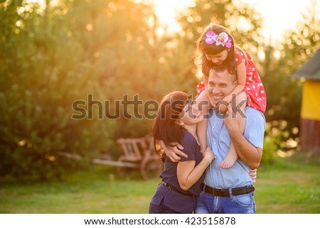 A happy family. Daughter kisses her mother whereas smiling father is carrying his daughter on his shoulders at nice sunny background.