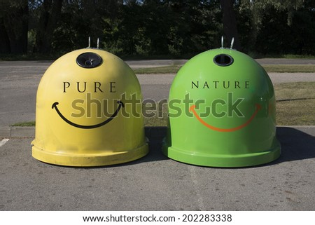 A large green and yellow recycling bin outdoors - stock photo