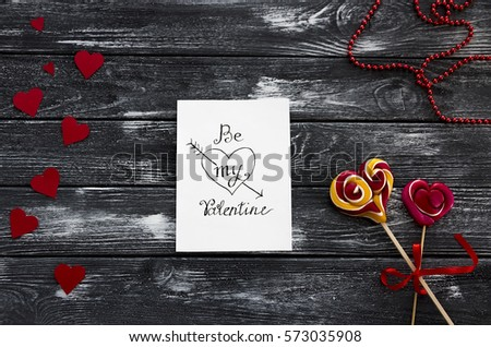 "A letter paper for Valentine's day with a gentle message ""Be my Valentine"" with paper red hearts,  sweets  Lollipop on Vintage texture table. Flat lay.  Saint Valentine Day celebration essentials."