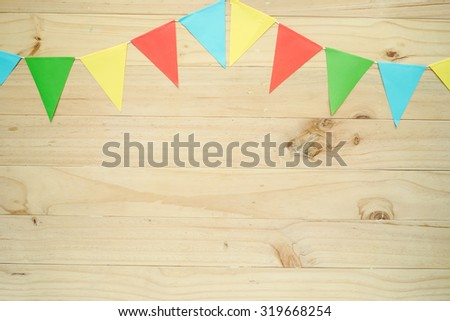 A line of colorful party flags, on wooden background - stock photo