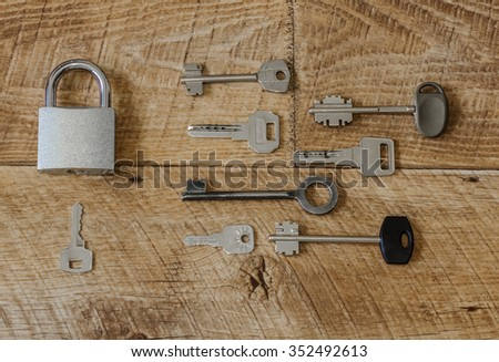 a lot of metal keys and a steel lock on a wooden boards / Many keys one lock