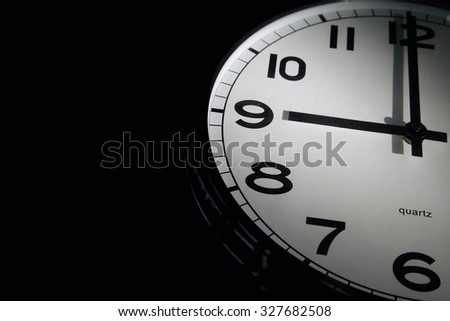 9 a.m. Clock on black background with space for text or image - stock photo