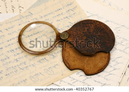a magnifying glass on some old letters