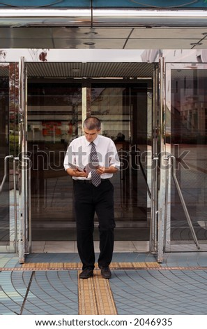A man (businessman or student....) reading with attention a notebook while is walking out from a modern building(corporate or library..... )